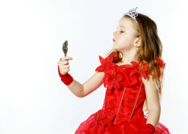 Little Girl Dressed As Royaly Looks In Mirror With Haughty Face
